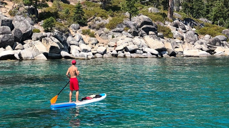 homme qui pratique du paddle gonflable en sup board